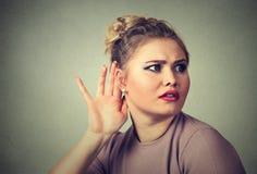 La mano entrometida de la mujer al gesto del oído escucha cuidadosamente secretamente adentro en la conversación del chisme foto de archivo libre de regalías