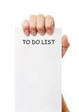 La mano era el sostenerse de a para hacer la nota de papel de la lista imagen de archivo
