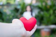 La mano es lleva a cabo un corazón rojo por la tarde para substituir el amor en la tarjeta del día de San Valentín Dé el corazón  imagenes de archivo