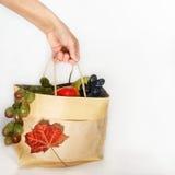 La mano escoge el paquete con la fruta fresca Foto de archivo libre de regalías