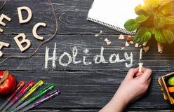 La mano escribe días de fiesta en un tablero negro de tableros de madera El concepto de una escuela primaria Caos creativo Escrit imagen de archivo