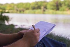 La mano escribe el lápiz de la pluma de la libreta cerca del lago en el parque en día soleado Foto de archivo