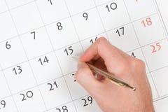 La mano escribe en calendario Imagen de archivo libre de regalías