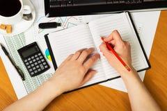 La mano escribe en cuaderno en blanco en lugar de trabajo con fotos de archivo libres de regalías