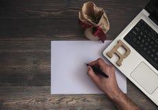 La mano escribe en cuaderno en la foto de la acción del ordenador portátil fotos de archivo