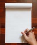 La mano escribe en el cuaderno Fotografía de archivo libre de regalías