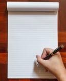 La mano escribe en el cuaderno con la pluma Fotos de archivo