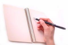 La mano escribe en un cuaderno Fotos de archivo libres de regalías