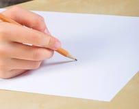 La mano escribe en un papel en blanco Fotos de archivo