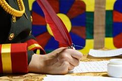 La mano escribe la pluma de canilla roja en el pergamino imágenes de archivo libres de regalías