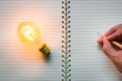 La mano escribe sobre el cuaderno Foto de archivo