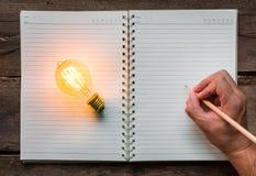 La mano escribe sobre el cuaderno Imágenes de archivo libres de regalías