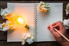 La mano escribe sobre el cuaderno y la bombilla Imagen de archivo