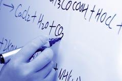 La mano escribe una fórmula química en un whiteboard. Foto de archivo libre de regalías