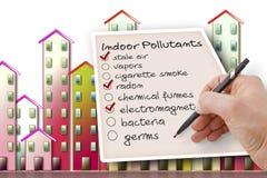 La mano escribe una lista de verificaci?n de agentes contaminadores de aire interior contra un fondo de los edificios fotografía de archivo libre de regalías