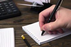 La mano escribe una pluma de bola y una calculadora Fotos de archivo libres de regalías