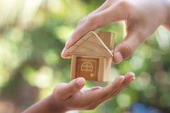 La mano está dando un modelo de una casa a la mano del niño imagenes de archivo