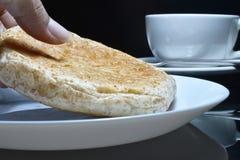 La mano está escogiendo el pan entero del grano en una placa blanca Fotos de archivo