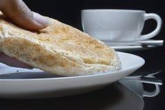 La mano está escogiendo el pan entero del grano en una placa blanca Imagen de archivo