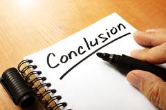 La mano está escribiendo la conclusión en una nota imagenes de archivo