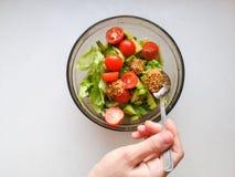 La mano está exprimiendo la cal sobre la ensalada vegetariana se hace del aguacate, de los tomates, del pepino y de la albahaca fotos de archivo