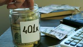 La mano está poniendo el dinero en tarro con la muestra 401k Plan de retiro almacen de metraje de vídeo