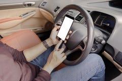 La mano está sosteniendo un teléfono del tacto con la pantalla aislada en el coche fotos de archivo libres de regalías