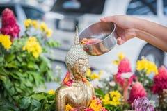 La mano está vertiendo el agua la estatua de Buda en ocasión de la canción Fotos de archivo