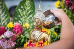 La mano está vertiendo el agua la estatua de Buda en ocasión de la canción Foto de archivo