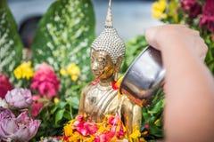 La mano está vertiendo el agua la estatua de Buda en ocasión de la canción Imagen de archivo