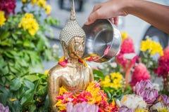 La mano está vertiendo el agua la estatua de Buda en ocasión de la canción Fotografía de archivo libre de regalías
