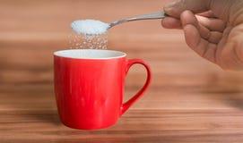 La mano está vertiendo el azúcar a la taza roja de té Concepto malsano de la consumición fotos de archivo