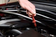 La mano estrae l'asta misura-livello dell'olio in un vano motore pulito dell'automobile Immagini Stock