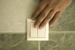 La mano extingue la luz en el cuarto de ba?o usando un interruptor de la pared imagen de archivo