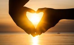 La mano fa il cuore con il tramonto immagine stock libera da diritti
