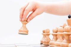 La mano fa il primo movimento del gioco di scacchi Fotografie Stock