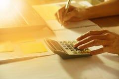 La mano facendo uso del calcolatore e la tenuta disegnano a matita per analizzare finanziario fotografia stock libera da diritti