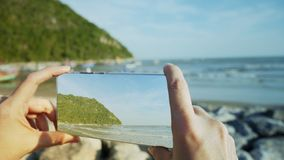 La mano facendo uso dello smartphone prende la foto alla spiaggia fotografia stock libera da diritti