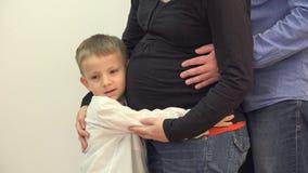 La mano feliz del niño y del padre abraza el vientre embarazada de la madre, detalle almacen de metraje de vídeo