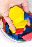 La mano femenina añade para arriba bloques coloreados de madera en la caja Fondo blanco, aislante DOF bajo Imágenes de archivo libres de regalías