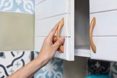 La mano femenina abre las puertas del armario, cierre fotos de archivo