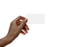 La mano femenina africana aislada sostiene la tarjeta blanca en un backgro blanco Imagen de archivo libre de regalías