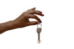 La mano femenina africana lleva a cabo llaves en el fondo blanco Foto de archivo