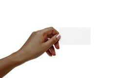 La mano femenina africana sostiene la tarjeta blanca en un fondo blanco Foto de archivo