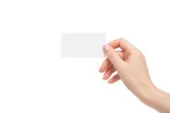 La mano femenina aislada sostiene la tarjeta blanca en un fondo blanco Foto de archivo libre de regalías