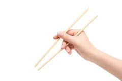La mano femenina aislada sostiene los palillos en un fondo blanco Fotografía de archivo