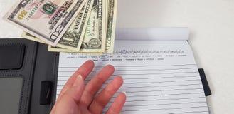 La mano femenina alcanza para los billetes de banco del dólar sobre el cuaderno abierto fotografía de archivo libre de regalías