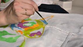 La mano femenina aplica la pintura azul en tela con un modelo usando un cepillo