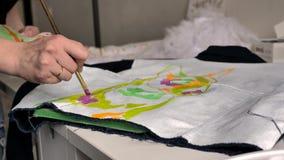 La mano femenina aplica la pintura rosada en tela con el modelo usando un cepillo