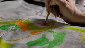 La mano femenina aplica la pintura rosada en tela con un modelo